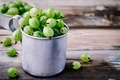 Fresh raw green gooseberries in a mug on wooden background. - PhotoDune Item for Sale