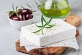 Homemade greek cheese feta with rosemary and herbs on cutting board with olive oil and olives - PhotoDune Item for Sale