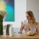 Beautiful Girl Sitting at Kitchen Table and Drinking Coffee - VideoHive Item for Sale
