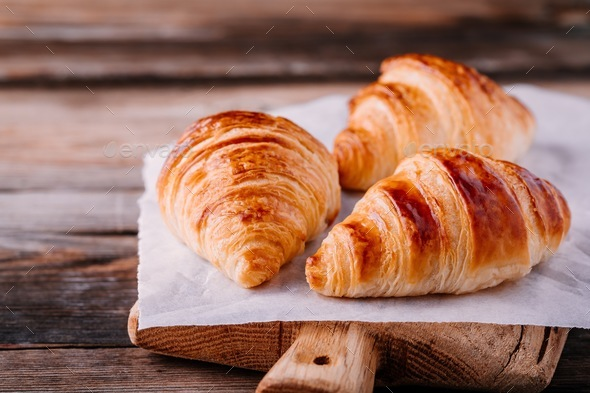 Homemade baked croissants on wooden rustic background - Stock Photo - Images