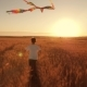 A Boy Runs Across the Field at Sunset with a Kite Flying Over His Head - VideoHive Item for Sale