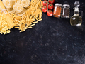 Variety of uncooked pasta next to spices, fresh tomatoes and sunflower oil - PhotoDune Item for Sale