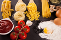 Four types of raw uncooked pasta next to tomatoe souce - PhotoDune Item for Sale