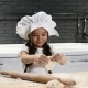 Little Pretty Girl in Chef Hat and Apron. Kid Chef Concept. Adorable Girl Playing with Dough - VideoHive Item for Sale