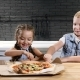 Two Children Eating Pizza Trying First Piece - VideoHive Item for Sale