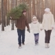 A Happy Family with a Child Is Walking Along a Snow-covered Forest - VideoHive Item for Sale