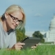 A Woman Resting on a Lawn Against the Background of the Capitol in Washington, USA. Uses a Tablet - VideoHive Item for Sale