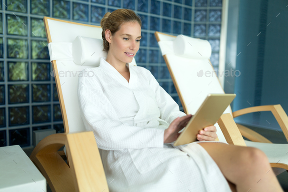Beautiful woman relaxing and using tablet in spa - Stock Photo - Images