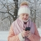 A Woman in a Pink Jacket Enjoys a Walk in a Winter Park. Uses a Mobile Phone - VideoHive Item for Sale