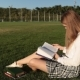 A Female Student in a Park Reading a Book - VideoHive Item for Sale