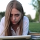 Female Student in a Park with Books and a Tablet - VideoHive Item for Sale