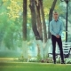 Handsome Young Man Is Waiting for Someone in the Park in the Summer or in the Spring - VideoHive Item for Sale