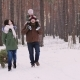 Two Parents with a Child Driving a New Year Tree on a Sled on a Snowy Forest - VideoHive Item for Sale