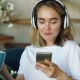 Happy Young Lady Is Using Smartphone Chatting Online and Listening To Music with Wireless Headphones - VideoHive Item for Sale