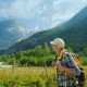 An Active Woman with a Backpack Walks Against the Backdrop of the Mountains and the Briksdal Glacier - VideoHive Item for Sale