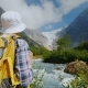A Tourist with a Yellow Backpack Looks at a Beautiful Glacier at the Top of the Mountain - VideoHive Item for Sale