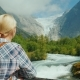 A Female Traveler Looks at the Beautiful Mountains and Glacier on Top. Briksdal Glacier in Norway - VideoHive Item for Sale