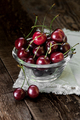 Red sweet cherry in a glass bowl on a dark wooden table close-up - PhotoDune Item for Sale