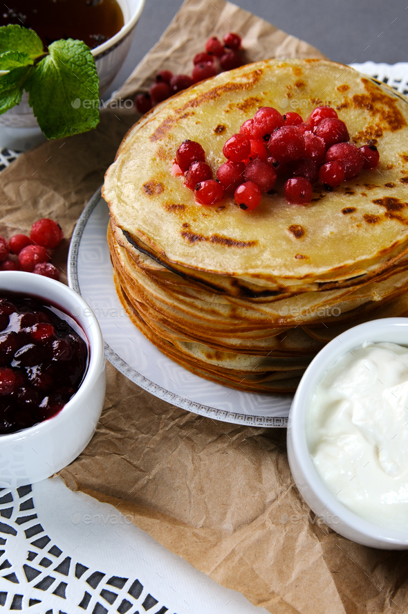 Stack of pancakes served with fresh cranberries, jam and cream o - Stock Photo - Images