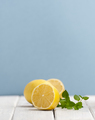 Half a ripe lemon and a mint branch on a white wooden table on a - PhotoDune Item for Sale