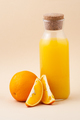 Fresh orange juice in a glass bottle and orange on a light beige - PhotoDune Item for Sale