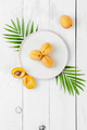 Ripe apricots on a round plate on a white board table. - PhotoDune Item for Sale