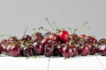 A handful of red cherries on a white wooden table in a crisp pla - PhotoDune Item for Sale