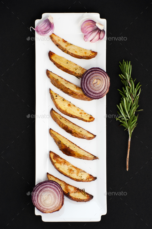 Baked potatoes and red lus with rosemary and garlic on a white r - Stock Photo - Images