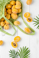 Apricots in a string bag and green leaves on a white board. - PhotoDune Item for Sale