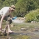 Thirsty Man Taking Bottle of Water From Mountain Stream and Drinking at Camping - VideoHive Item for Sale