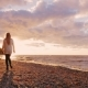 Young Woman Walking with a Dog on the Shore of Lake Ontario at Sunset - VideoHive Item for Sale