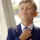 Funny Little First-grader Boy Is Wearing Formal Suit, Correcting Tie, Smiling - VideoHive Item for Sale