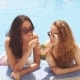 Outdoor Portrait of Two Young Cute Girlfriends in Sunglasses and Swimsuits with Cocktail Glass - VideoHive Item for Sale