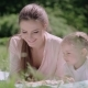 Young Mother And Daughter Reading Book Lying On Grass At Park - VideoHive Item for Sale