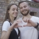 Portrait of an Attractive Young Europian Couple Laughing and Making a Heart Shape with Their Hands - VideoHive Item for Sale