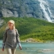 The Traveler Walks Among the Majestic Cliffs with Waterfalls and Glaciers on Top - VideoHive Item for Sale