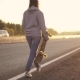 Girl in Headphones and with a Skateboard in Her Hands Walking Along the Highway - VideoHive Item for Sale