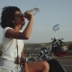 A Latino , Curley Haired Girl Is Thirsty Drinking Her Water and Is Sitting on Her Bike By the Road - VideoHive Item for Sale
