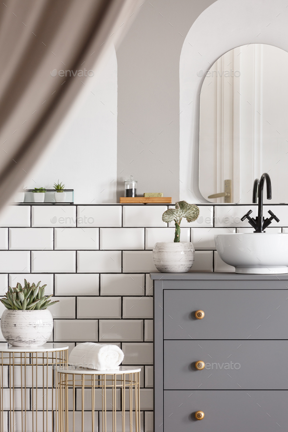 Mirror above grey cabinet with washbasin in bright bathroom inte - Stock Photo - Images