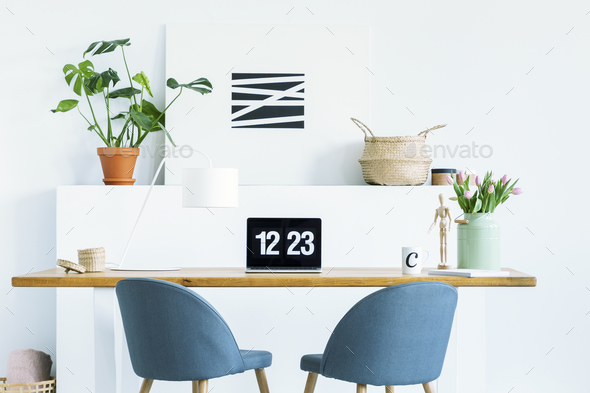 Blue chairs at wooden desk with laptop in white work area with p Stock Photo by bialasiewicz