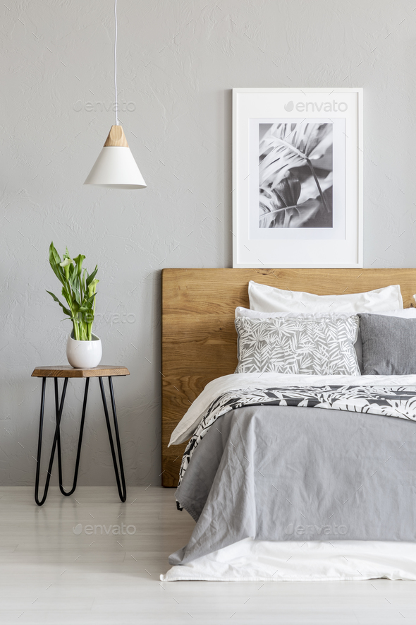 Plant On Table Next To Wooden Bed In Grey Bedroom Interior With Stock Photo