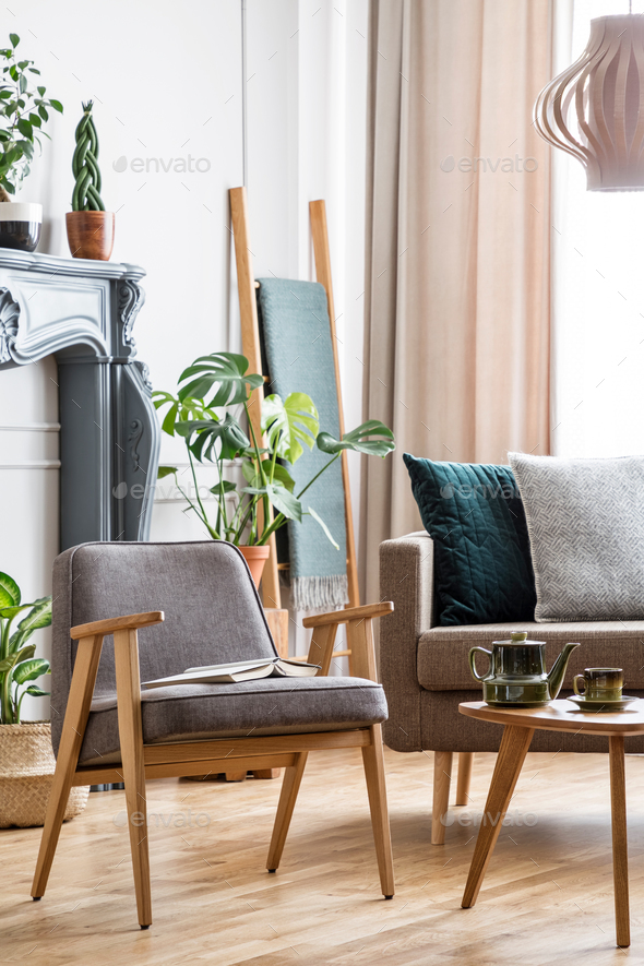 Real photo of a chair standing next to a coffee table and a sofa - Stock Photo - Images