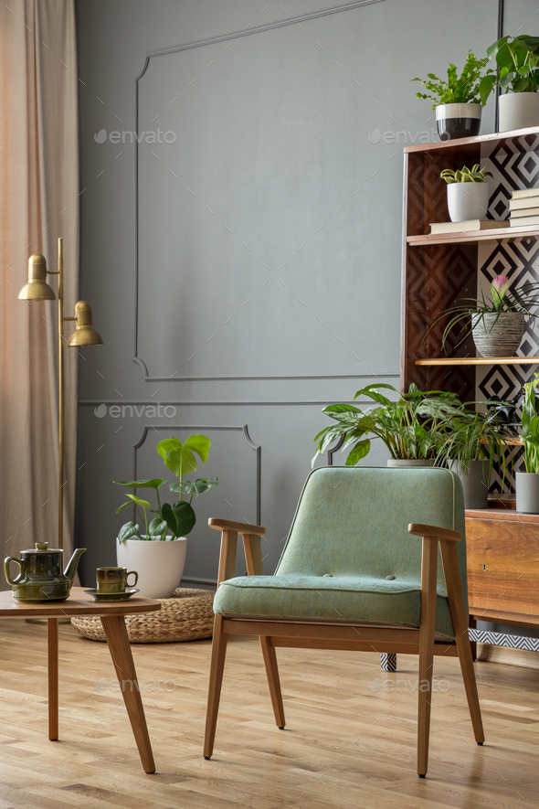 Green armchair next to wooden table in grey vintage living room
