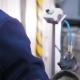 Backside View Worker Twists Screws on Accumulators on Conveyor