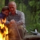 Elderly Couple in the Woods By the Fire in a Pine Forest - VideoHive Item for Sale