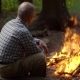 Elderly Single Man Basking By the Fire in a Pine Forest - VideoHive Item for Sale