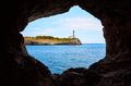 Portocolom Lighthouse on a cliff seen from a cave. - PhotoDune Item for Sale