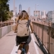 Back View Happy Woman with Backpack Riding a Bicycle Along a Separate Bike Lane Level on Brooklyn - VideoHive Item for Sale