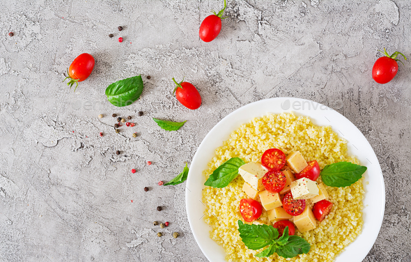 Millet porridge with cheese, butter and basil in white bowl.  - Stock Photo - Images