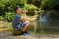 Boy drinks water from bottle outdoors sitting on stone - PhotoDune Item for Sale